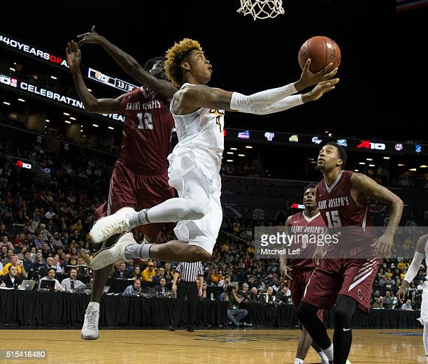 Justin Tillman of the Virginia Commonwealth Rams takes a shot against Papa Ndao of the Saint Joseph's Hawks in the championship game of the men's...