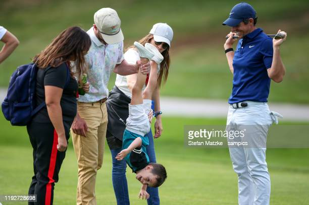 Justin Timberlake lifts up his son Silas next to his wife Jessica Biel and Rory McIlroy of Northern Ireland ahead of the ProAm prior to the start of...