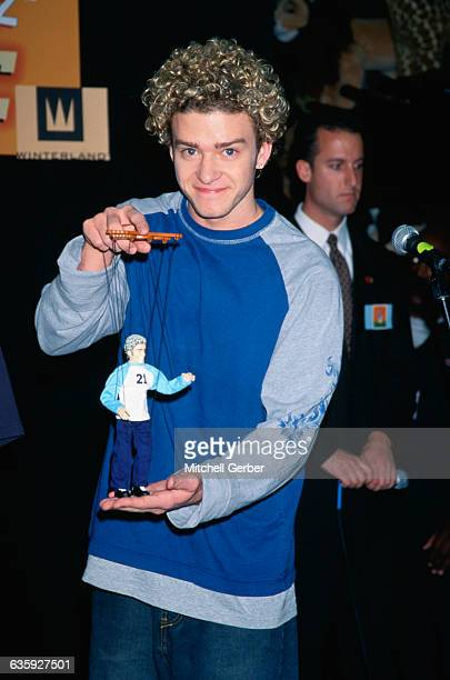 Justin Timberlake of the superstar group N'Sync holds his look alike toy marionette during the unveiling of the new dolls at New York's Fao Schwarz
