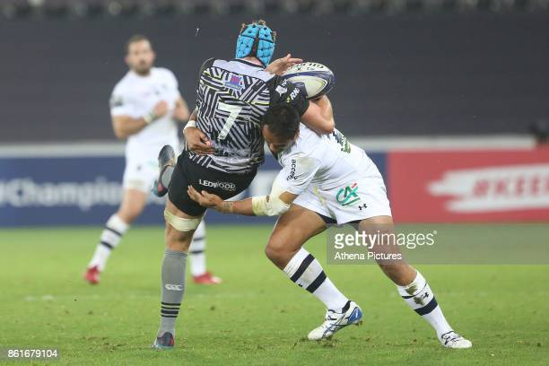 Justin Tipuric of Ospreys is tackled by Peter Betham of Clermont during the Champions Cup Round 1 match between Ospreys and Clermont at The Liberty...