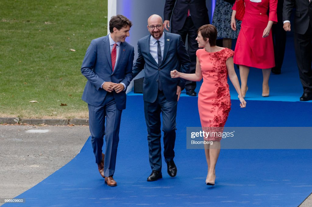 Justin Trudeau, Canada's prime minister, left, walks with Charles Michel, Belgium's prime minister, center, and Amelie Derbaudrenghien, partner of Belgium's prime minister, as they arrive for a working dinner during the North Atlantic Treaty Organization (NATO) summit at the museum of art and history in Cinquantenaire park in Brussels, Belgium, on Wednesday, July 11, 2018. President Donald Trump opened up another front in his tussle with allies on his arrival at NATOs annual summit, targeting Germany over its support for the Nord Stream 2 gas pipeline from Russia. Photographer: Marlene Awaad/Bloomberg via Getty Images