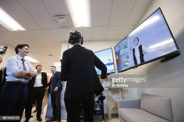 Justin Trudeau Canada's prime minister left watches a demonstration of a virtual reality program during a tour of the Bayview Yards innovation center...