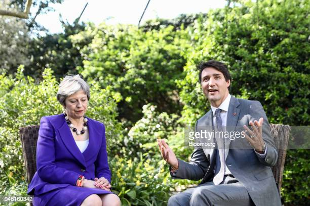 Justin Trudeau Canada's prime minister right gestures while speaking to Theresa May UK prime minister during a bilateral meeting in the gardens of...