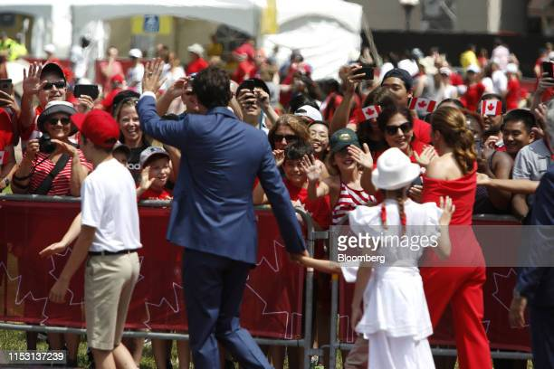 Justin Trudeau Canada's prime minister second left waves at attendees while arriving with his family to a Canada Day event on Parliament Hill in...