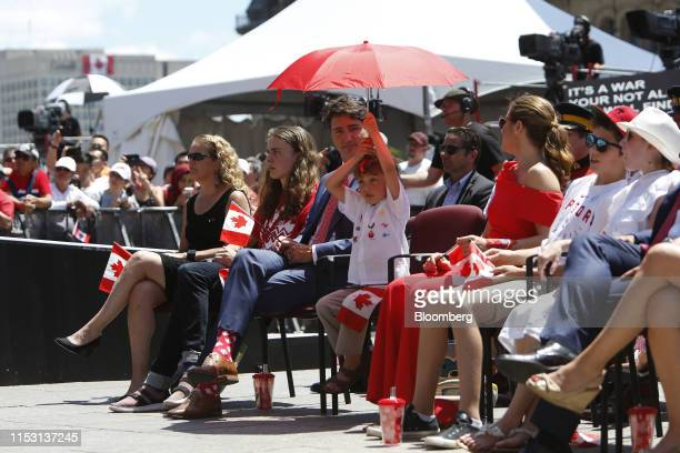 Justin Trudeau Canada's prime minister watches as his son holds an umbrella during a Canada Day event on Parliament Hill in Ottawa Ontario Canada on...