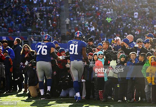 Justin Tuck and Chris Snee of the New York Giants of the New York Giants greet families of Sandy Hook Elementary School before the game against the...