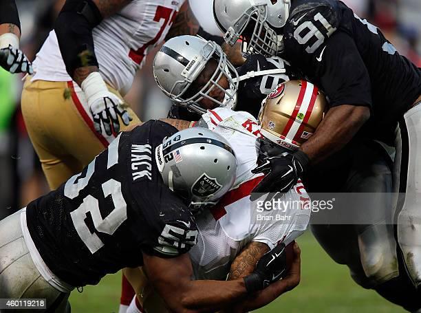 Justin Tuck of the Oakland Raiders Antonio Smith of the Oakland Raiders Khalil Mack of the Oakland Raiders sack Colin Kaepernick of the San Francisco...