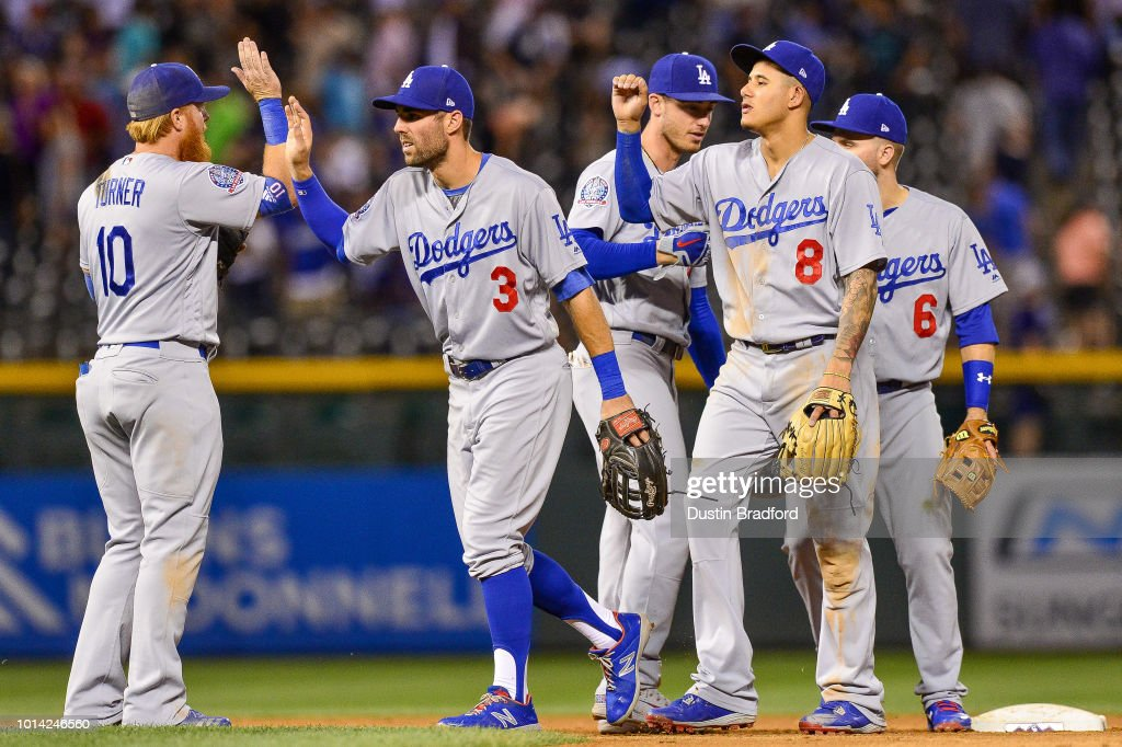 Justin Turner #10, Chris Taylor #3, Manny Machado #8, Cody Bellinger #35, and Brian Dozier #6 of the Los Angeles Dodgers celebrate after an 8-5 win over the Colorado Rockies at Coors Field on August 9, 2018 in Denver, Colorado.