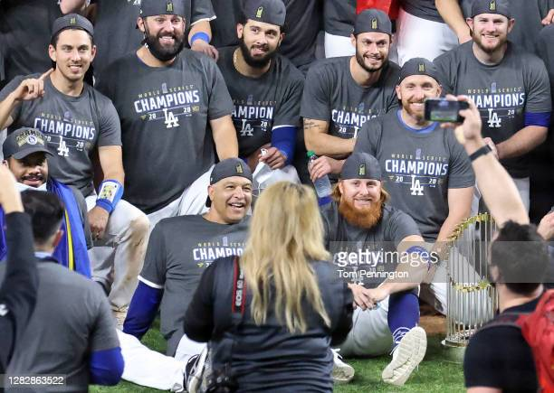 Justin Turner of the Los Angeles Dodgers and manager Dave Roberts of the Los Angeles Dodgers pose for a photo with their teammates after the teams...