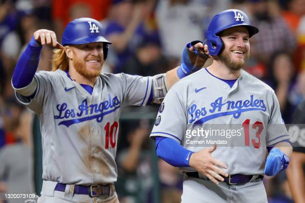 Justin Turner of the Los Angeles Dodgers and Max Muncy react after scoring during the sixth inning against the Houston Astros at Minute Maid Park on...