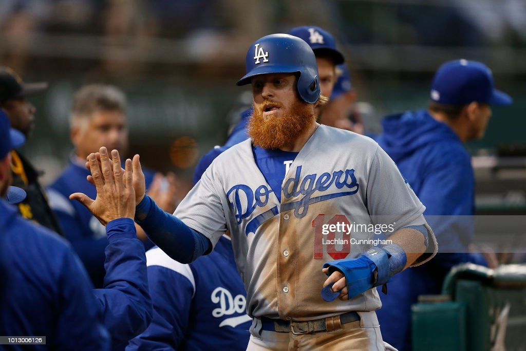 Justin Turner #10 of the Los Angeles Dodgers celebrates after scoring a run on a single hit by teammate Cody Bellinger #35 in the third inning against the Oakland Athletics at Oakland Alameda Coliseum on August 7, 2018 in Oakland, California.