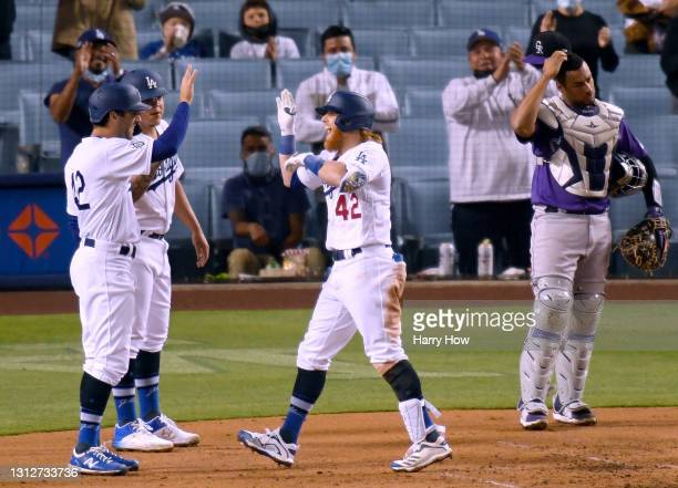 Justin Turner of the Los Angeles Dodgers celebrates his three run homerun with Julio Urias and Chris Taylor, past Elias Diaz of the Colorado Rockies,...