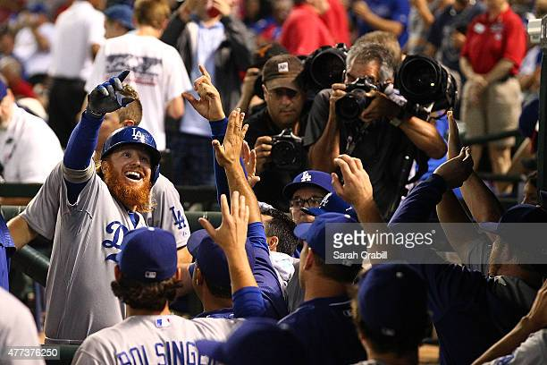 Justin Turner of the Los Angeles Dodgers celebrates in the dugout after hitting a tworun homer in the ninth inning during a game against the Texas...