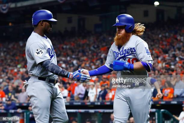Justin Turner of the Los Angeles Dodgers celebrates scoring on a RBI single during the first inning with Yasiel Puig against the Houston Astros in...