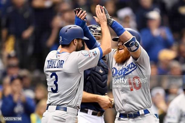 Justin Turner of the Los Angeles Dodgers celebrates with Chris Taylor after hitting a two run home run against Jeremy Jeffress of the Milwaukee...