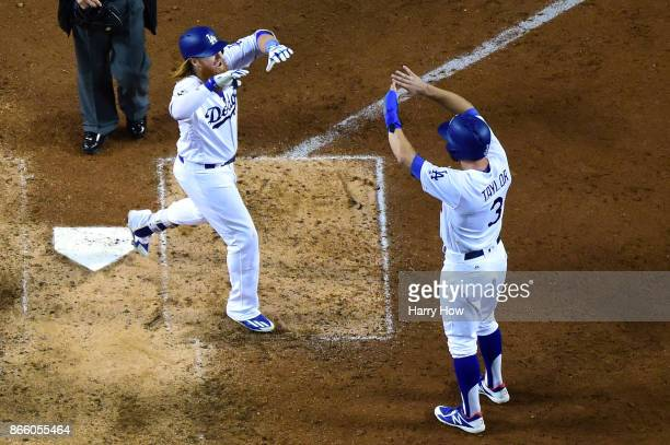 Justin Turner of the Los Angeles Dodgers celebrates with Chris Taylor after hitting a tworun home run during the sixth inning against the Houston...