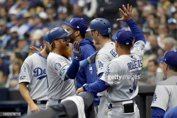 Justin Turner of the Los Angeles Dodgers celebrates with Cody Bellinger and manager Dave Roberts after hitting a two run home run against Jeremy...
