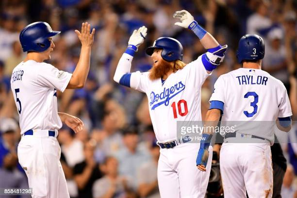 Justin Turner of the Los Angeles Dodgers celebrates with Corey Seager and Chris Taylor after Turner hits a threerun home run in the first inning...