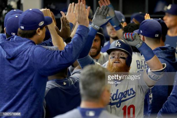 Justin Turner of the Los Angeles Dodgers celebrates with his teammates in the dugout after hitting a two run home run against Jeremy Jeffress of the...