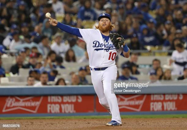 Justin Turner of the Los Angeles Dodgers fields a ground ball near the third base line during the sixth inning of the MLB game against the San Diego...