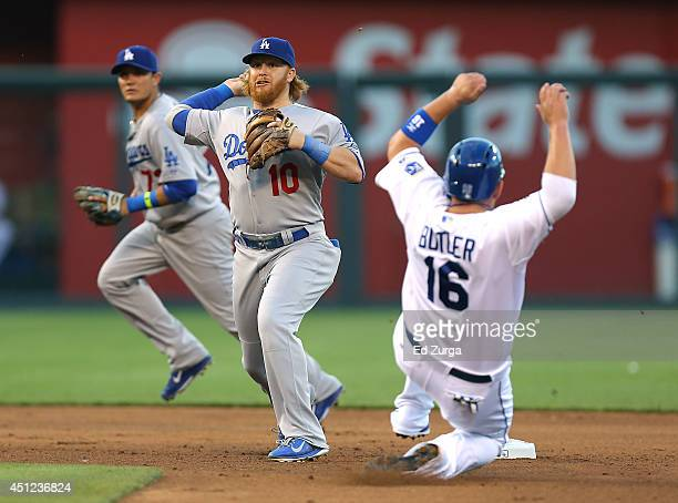 Justin Turner of the Los Angeles Dodgers gets the force out on Billy Butler of the Kansas City Royals and throws to first on a double play attempt in...