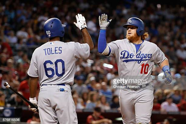 Justin Turner of the Los Angeles Dodgers high fives Andrew Toles after hitting a solo home run against the Arizona Diamondbacks during the eighth...
