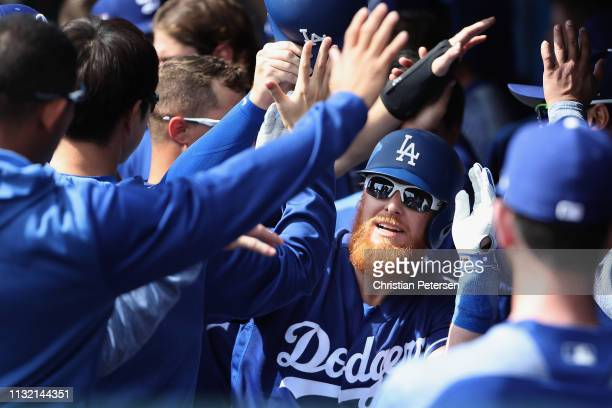 Justin Turner of the Los Angeles Dodgers high fives teammates in the dugout after hitting a tworun home run against the Chicago Cubs during the first...