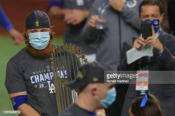 Justin Turner of the Los Angeles Dodgers holds the Commissioners Trophy after the teams 3-1 victory against the Tampa Bay Rays in Game Six to win the...