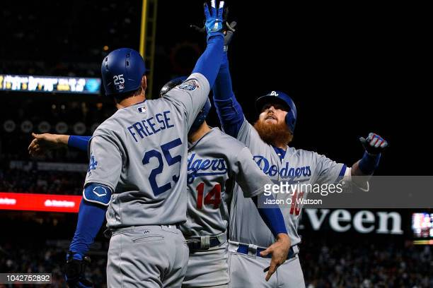 Justin Turner of the Los Angeles Dodgers is congratulated by David Freese and Enrique Hernandez after hitting a two run home run against the San...