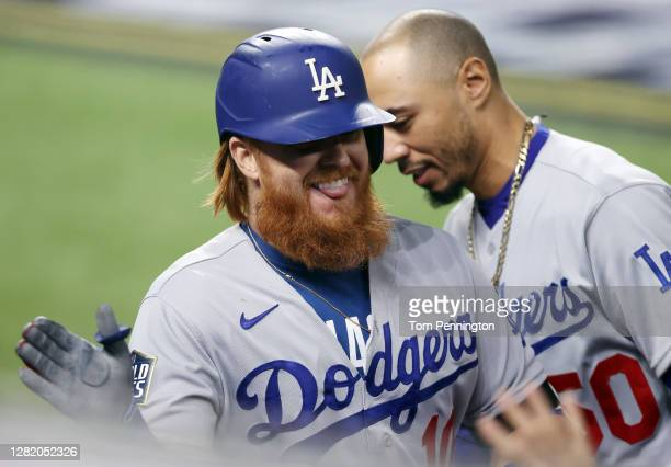 Justin Turner of the Los Angeles Dodgers is congratulated by his teammates after hitting a solo home run against the Tampa Bay Rays during the first...