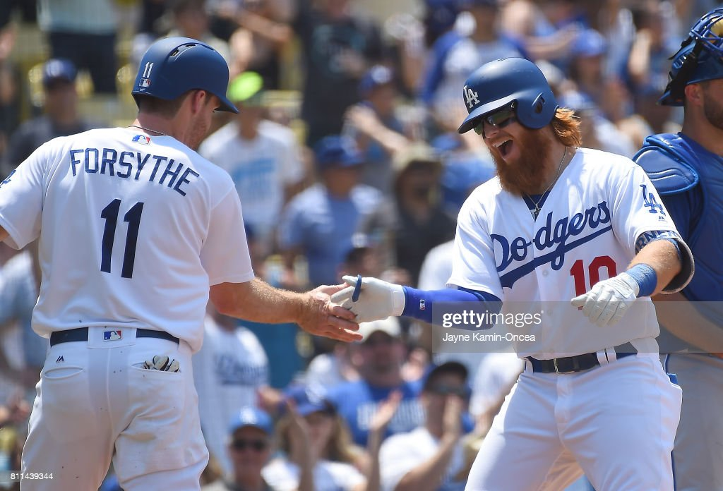 Justin Turner #10 of the Los Angeles Dodgers is greeted by Logan Forsythe #11, who scored on his two run shot in the third inning against the Kansas City Royals at Dodger Stadium on July 9, 2017 in Los Angeles, California.