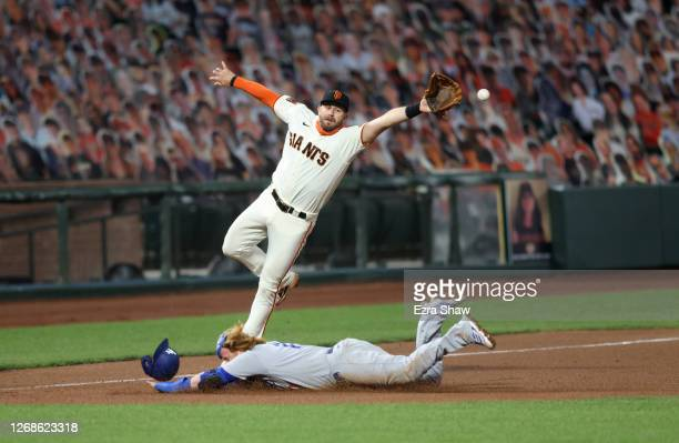 Justin Turner of the Los Angeles Dodgers safely steals third base as the ball gets past Evan Longoria of the San Francisco Giants in the tenth inning...