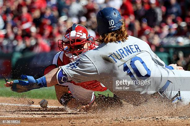 Justin Turner of the Los Angeles Dodgers scores against Jose Lobaton of the Washington Nationals on a single RBI hit by Josh Reddick of the Los...