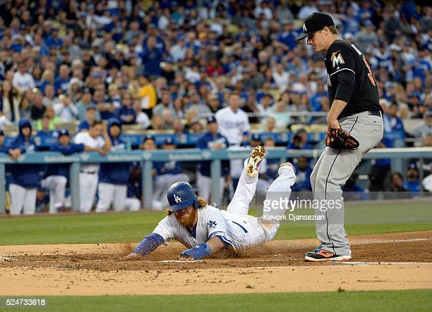 Justin Turner of the Los Angeles Dodgers slides at home plate to score a run after a wild pitch by pitcher Tom Koehler of the Miami Marlins during...