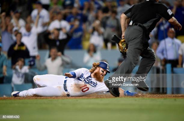 Justin Turner of the Los Angeles Dodgers touches home plate as he score the winning run after a double by pinch hitter Kyle Farmer who made his Major...