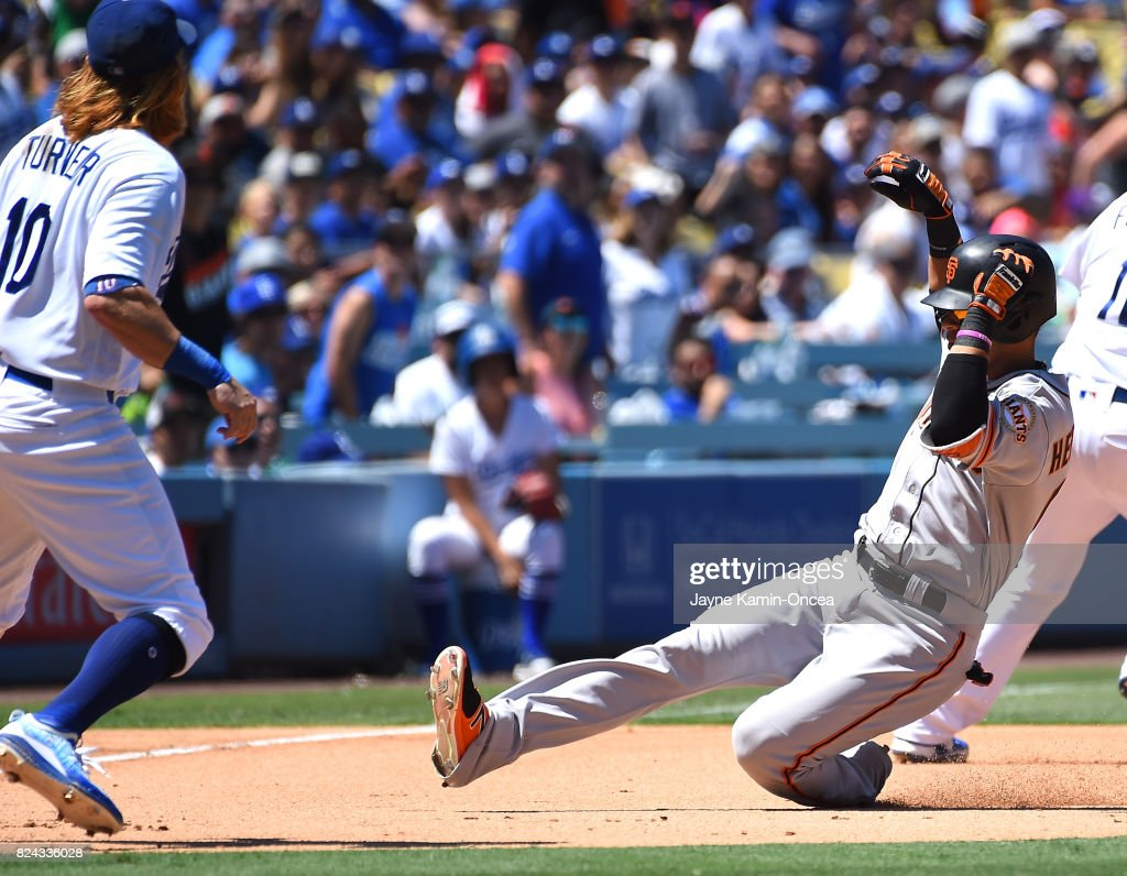 Justin Turner #10 of the Los Angeles Dodgers waits for the throw as Gorkys Hernandez #66 of the San Francisco Giants doubles and gets to third base on an error by Chris Taylor #3 of the Los Angeles Dodgers in the fifth inning of the game at Dodger Stadium on July 29, 2017 in Los Angeles, California.
