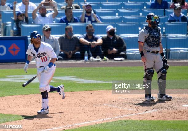 Justin Turner of the Los Angeles Dodgers watches his solo homerun with Jonathan Lucroy of the Washington Nationals, for a 1-0 lead in the sixth...