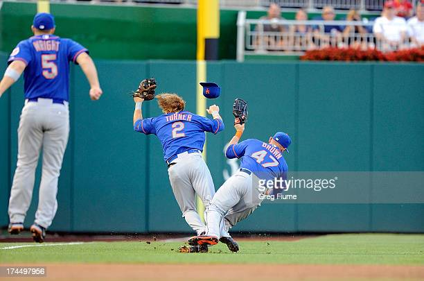 Justin Turner of the New York Mets collides with Andrew Brown after making a catch in the first inning against the Washington Nationals at Nationals...