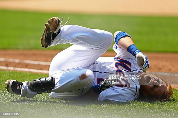 Justin Turner of the New York Mets reacts in pain after a fall diving back to first base during a run down against the Philadelphia Phillies during...