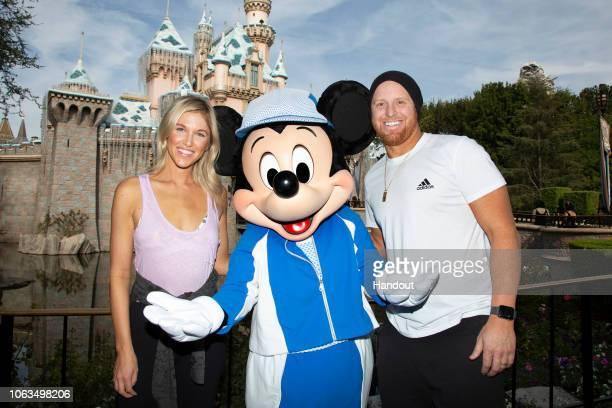 Justin Turner third baseman for the Los Angeles Dodgers and Kourtney Turner meet Mickey Mouse while visiting Disneyland park on November 4 2018 in...