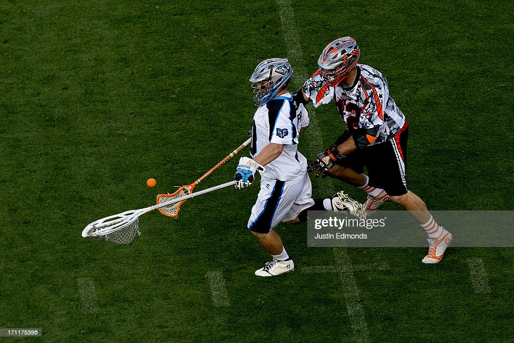 Justin Turri #12 of the Denver Outlaws knocks the ball loose from goaltender Brian Phipps #30 of the Ohio Machine during the second quarter at Sports Authority Field at Mile High on June 22, 2013 in Denver, Colorado.