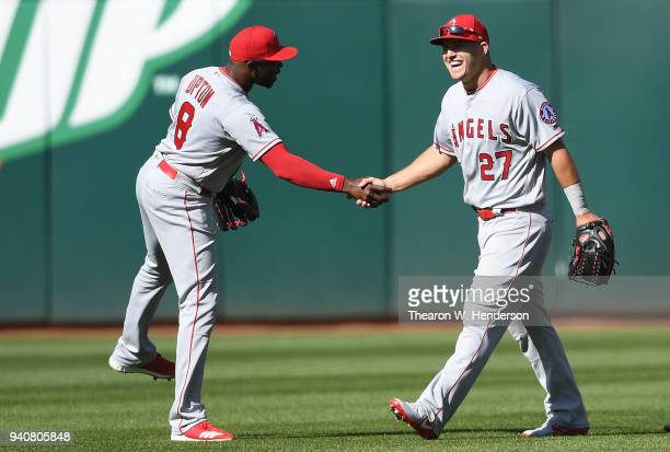Justin Upton and Mike Trout 27 of the Los Angeles Angels of Anaheim celebrate defeating the Oakland Athletics 7-4 at Oakland Alameda Coliseum on...