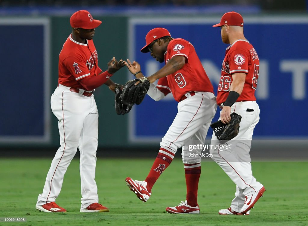 Justin Upton #8, Eric Young Jr. #9 and Kole Calhoun #56 of the Los Angeles Angels of Anaheim celebrate the 11-5 win over the Seattle Mariners at Angel Stadium on July 28, 2018 in Anaheim, California.
