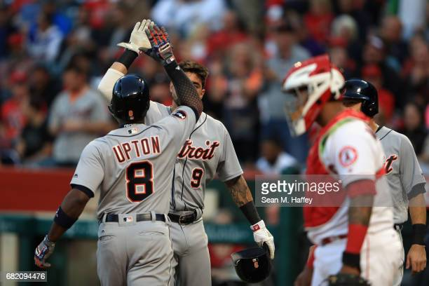 Justin Upton is congratulated by Nicholas Castellanos of the Detroit Tigers at the plate after hitting a threerun homerun during the first inning of...