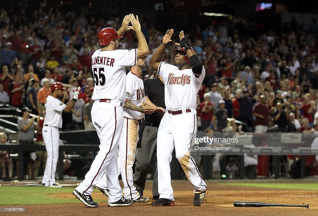 Justin Upton #10 of the Arizona Diamondbacks high-fives teammates Josh Collmenter #55 and Ryan Roberts #14 after all scored on a triple hit by Stephen Drew (not pictured) during the fifth inning of the Major League Baseball game against the Washington Nationals at Chase Field on June 3, 2011 in Phoenix, Arizona.