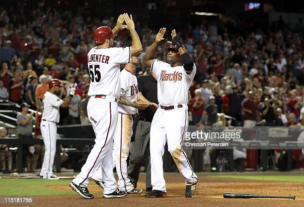 Justin Upton of the Arizona Diamondbacks highfives teammates Josh Collmenter and Ryan Roberts after all scored on a triple hit by Stephen Drew during...