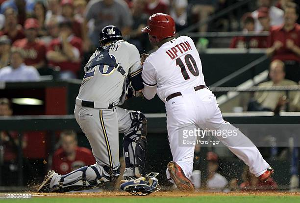 Justin Upton of the Arizona Diamondbacks is tagged out at home by catcher Jonathan Lucroy of the Milwaukee Brewers in the third inning in Game Three...