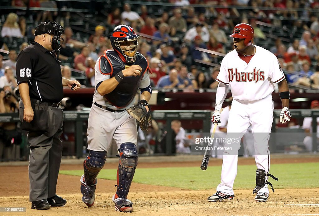 Justin Upton #10 of the Arizona Diamondbacks reacts to home plate umpire Eric Cooper after being called out on strikes as catcher Yadier Molina #4 of the St. Louis Cardinals reacts during the eighth inning of the Major League Baseball game at Chase Field on June 11, 2010 in Phoenix, Arizona.