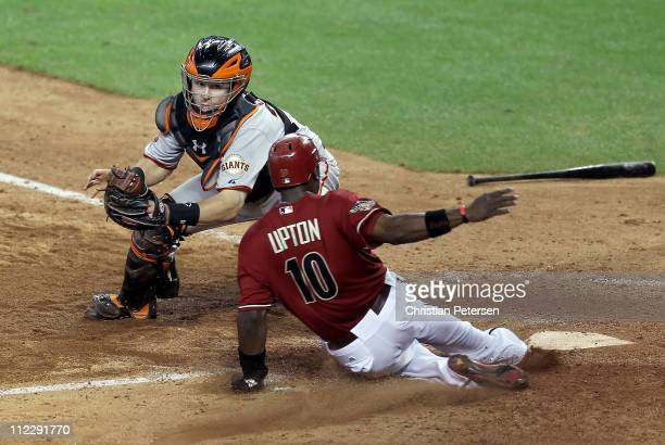 Justin Upton of the Arizona Diamondbacks safely slides in to score the game winning run past the tag from catcher Buster Posey of the San Francisco...