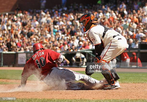 Justin Upton of the Arizona Diamondbacks scores on a sac fly by Chris Young while Bengie Molina of the San Francisco Giants covers home plate at ATT...